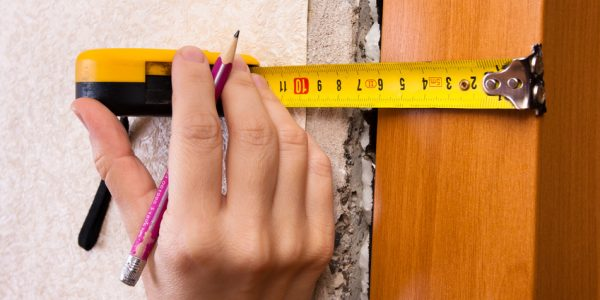 hands measuring wall with tape measure, closeup